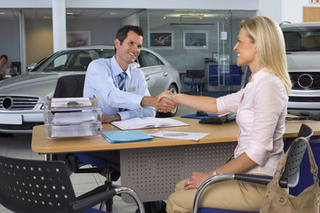 Car salesman and female customer sitting at desk in large car showroom, shaking hands, smiling