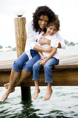 mother squeezing son sitting on jetty