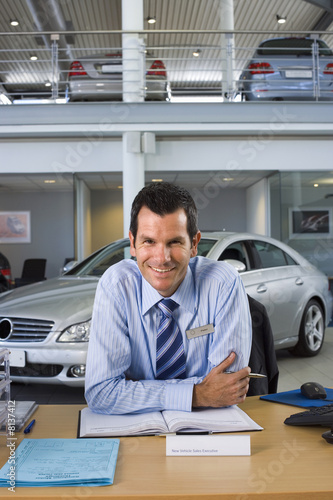 Car salesman sitting at desk in car showroom, smiling, front view, portrait