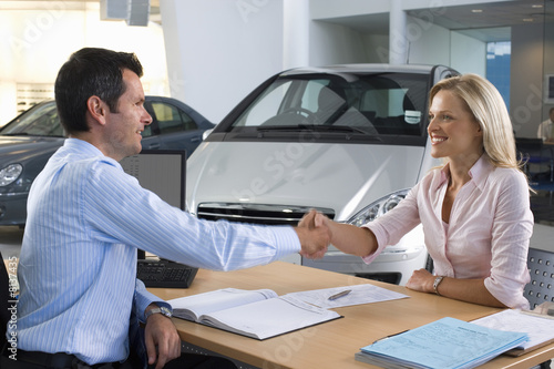Car salesman and female customer sitting at desk in car showroom, shaking hands, smiling, side view
