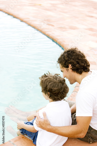 father and son sitting on the edge of swimming pool