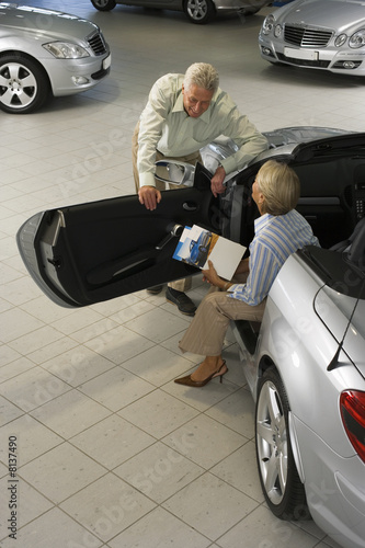 Senior couple looking at silver convertible car in large showroom, woman sitting in passenger seat, man leaning on door, elevated view