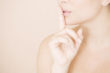 Close-up of woman holding a finger to her lips, speak no evil