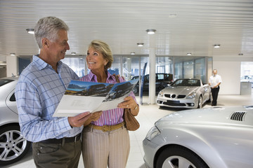 Senior couple standing in large car showroom, looking at brochure, smiling