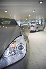 New silver saloon and convertible cars parked in large showroom, focus on foreground