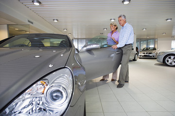 Senior couple looking at new silver convertible car in large showroom, man opening car door, smiling