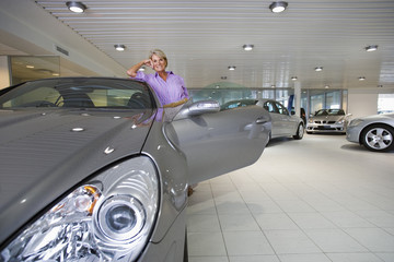 Senior woman looking at new silver convertible car in large showroom, leaning on roof, smiling, front view, portrait