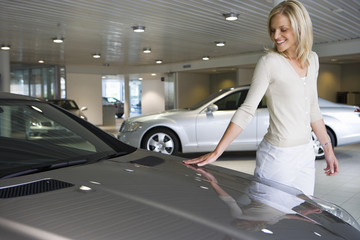 Woman stroking bonnet of new silver car in large showroom, smiling, side view