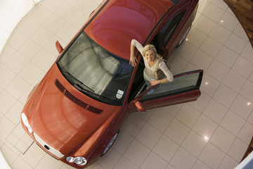 Woman leaning against new red hatchback in large car showroom, smiling, portrait, overhead view