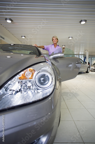 Senior woman looking at new silver convertible car in large showroom, front view, portrait