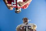 American football player running with ball at opposing player during competitive game, upward view
