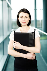 Young businesswoman standing on office walkway holding folder of papers