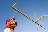 American football player, in red football strip and protective helmet, standing below goal post, arms folded, portrait, low angle view