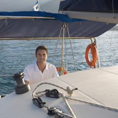 A man holding the wheel of a sailing boat