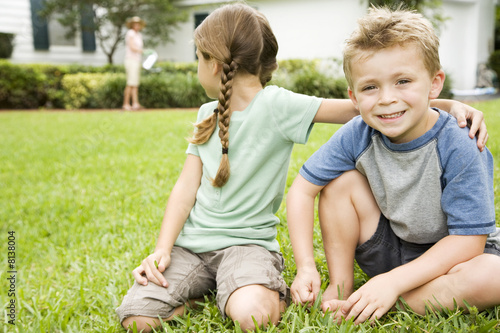 girl and boy sitting on lawn, girl looking behind her
