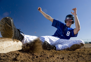 Baseball player, in blue uniform, sliding safely into base on pitch during competitive game (surface level, blurred motion)