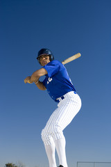 Baseball batter standing against clear blue sky, preparing to hit ball, front view, low angle view