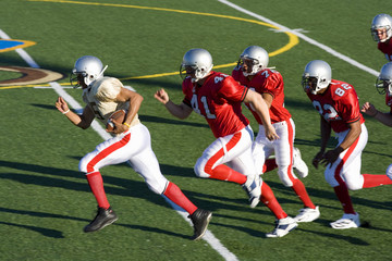 American football players chasing opposing player running with ball at speed during competitive game, side view