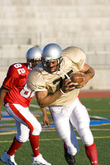 American football player chasing opposing player running with ball during competitive game