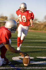 American football player attempting to kick field goal, teammate holding ball vertically against pitch