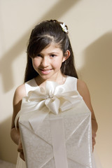 Girl (8-10), dressed in bridesmaid dress, holding wedding gift, smiling, front view, portrait