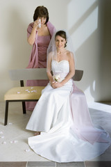 Bride in wedding dress sitting on bench, mother standing behind, wiping away tears of joy with handkerchief, smiling, portrait