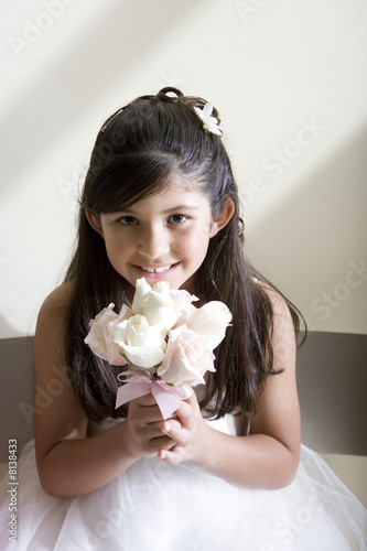 Girl (8-10), dressed in bridesmaid dress, holding wedding flowers, smiling, front view, portrait