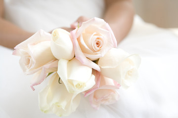 Bridesmaid (8-10) holding small bunch of white roses, close-up, mid-section