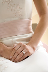 Bride sitting on chair at wedding, focus on wedding ring, close-up, mid-section