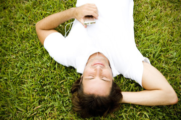 Man lying on the grass listening to personal stereo