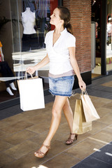 Woman with shopping bags walking down the street