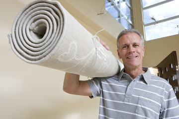 Senior man carrying rolled-up carpet on shoulder, moving house, smiling, low angle view, portrait