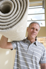 Senior man carrying rolled-up carpet on shoulder, moving house, smiling, low angle view, front view, portrait