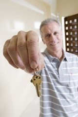 Senior man holding aloft set of keys to new house, smiling, front view, portrait