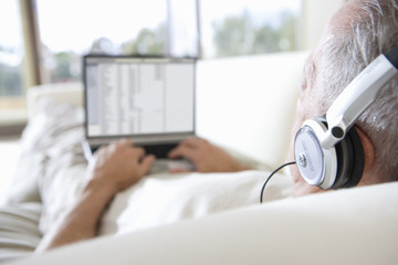 Senior man relaxing on sofa at home, listening to music on headphones, using laptop, rear view, focus on foreground