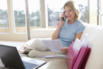 Mature woman sitting on sofa with laptop, holding document, using mobile phone, smiling, side view