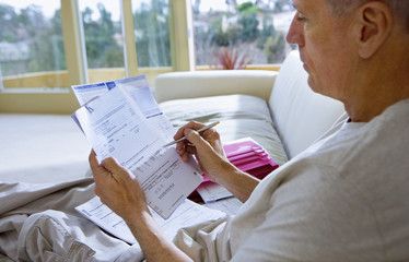 Senior man sitting on sofa at home, looking at bills, close-up, side view