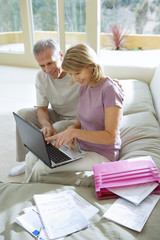 Senior couple sitting on sofa at home, using laptop, smiling, side view, pink folder and bills in foreground