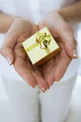 Mature woman holding small gold gift box in cupped hands, close-up, front view, mid-section
