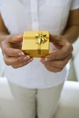 Mature woman holding small gold gift box in hands, close-up, front view, mid-section