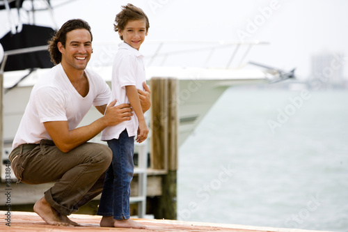 father and son on dock in marina
