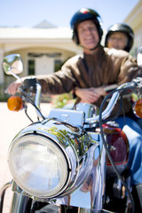Senior couple sitting on motorbike on driveway, smiling, portrait, focus on headlight in foreground