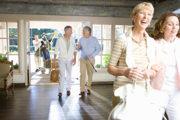 Two mature couples entering hotel foyer, man pushing luggage trolley through doorway in background, men talking golf, women smiling in foreground
