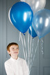 boy looking up at balloons he's holding