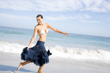 A young woman running on the beach