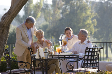 Two mature couples dining at outdoor restaurant table, standing couple placing hands affectionately on shoulders of seated friends, smiling