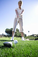 Mature woman preparing to tee off with driver on golf course (surface level)