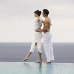 A couple balancing at the edge of a pool