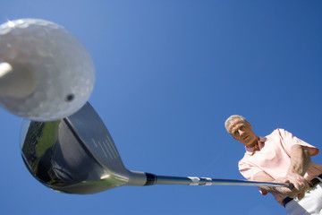 Mature man preparing to tee off on golf course, holding driver, close-up, upward view (wide angle)