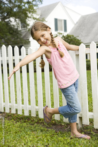 little girl posing standing by picket fence